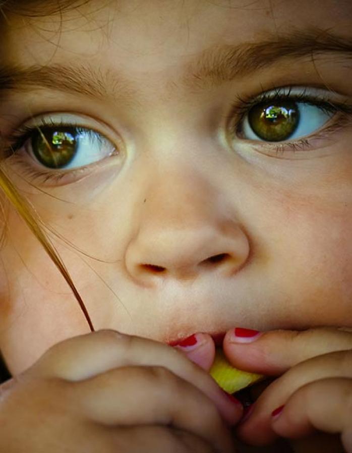 A kid eating fruit